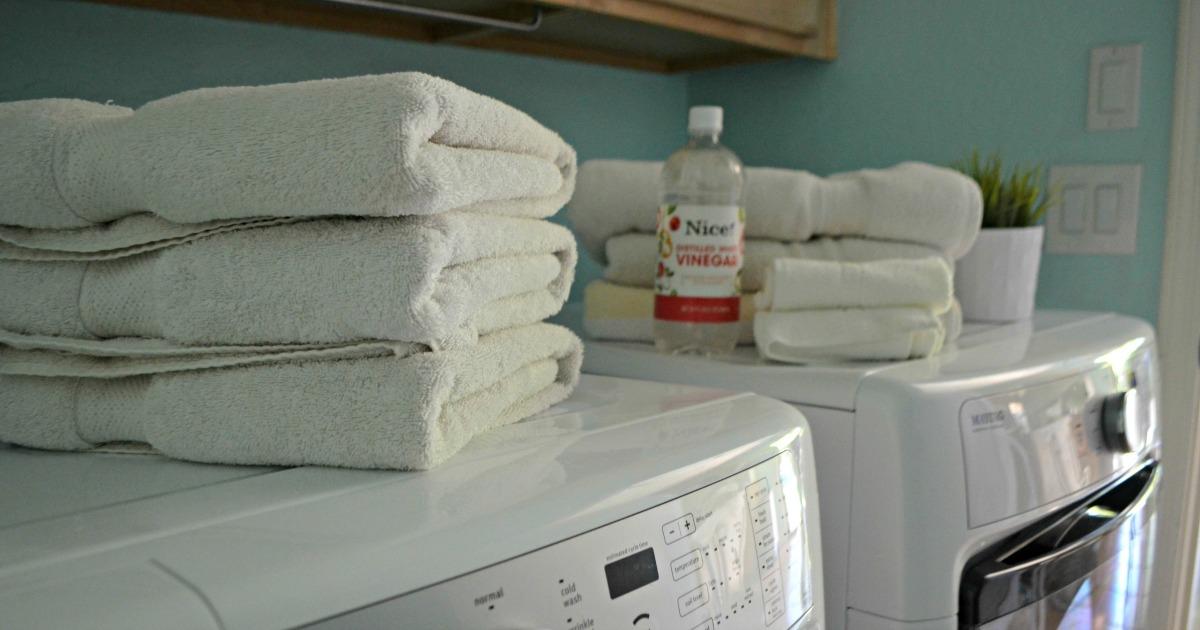 towels folded on a dryer near a bottle of white vinegar