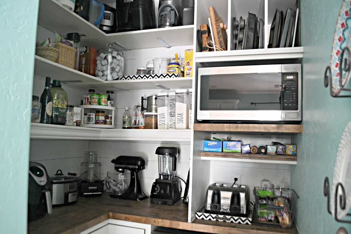 pantry with added shelves, microwave, and pantry items