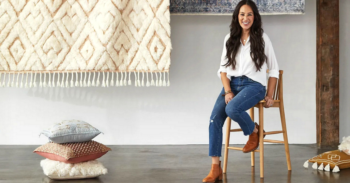 Joanna Gaines sitting next to pillows and rugs