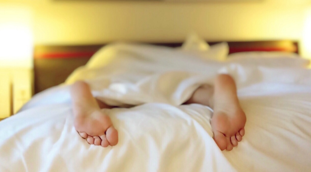 Person sleeping on bed tossing and turning