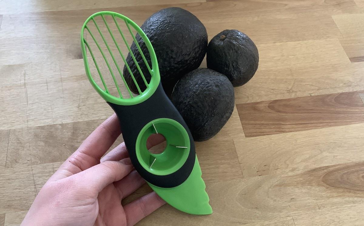 green avocado peeler knife with ripe avocados on the counter