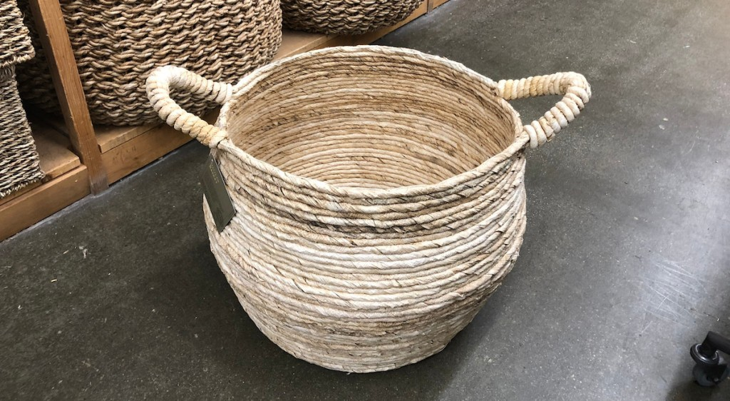 round natural woven basket with handles sitting on the floor