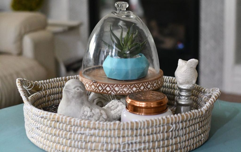 shallow basket tray with plant and candle sitting on counter