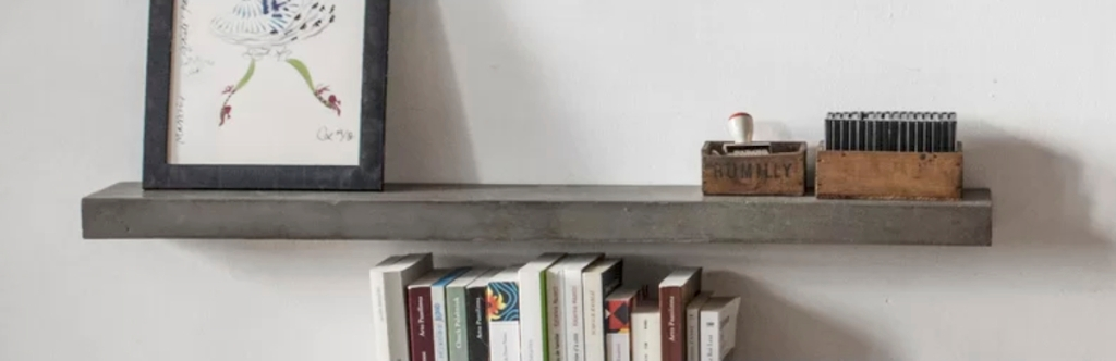 concrete shelf on wall with books and other accessories