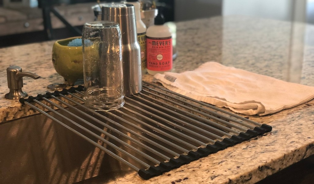 metal drying rack sitting over kitchen sink with two wet cups sitting on top