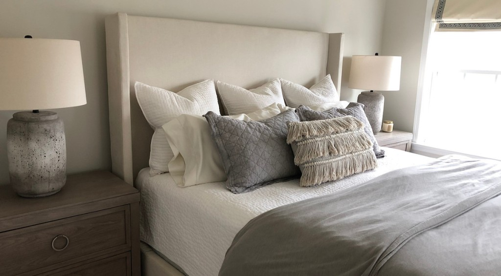 eight pillows on bed
