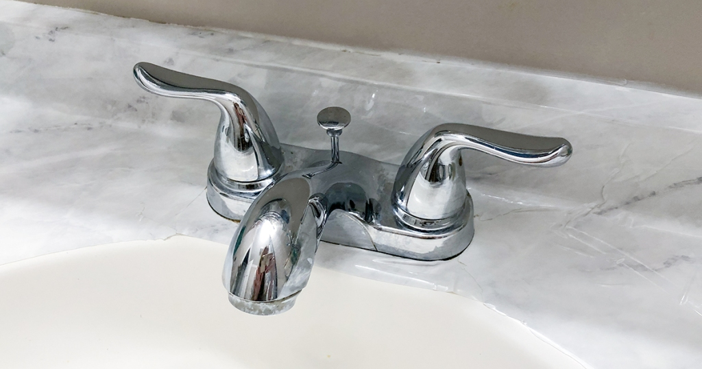 close of up faucet with marble contact paper around it