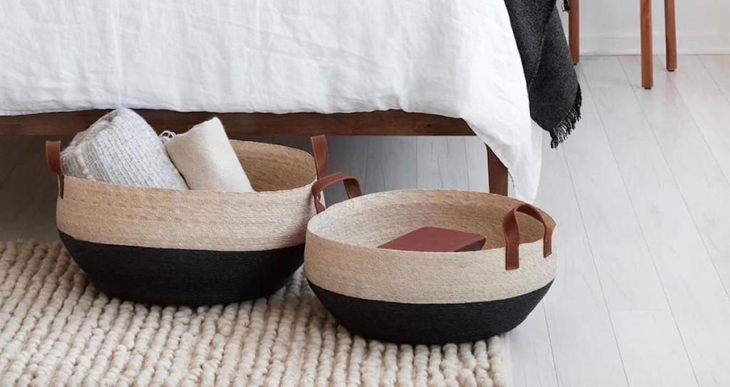 two tone black and white baskets sitting on the floor under bed frame