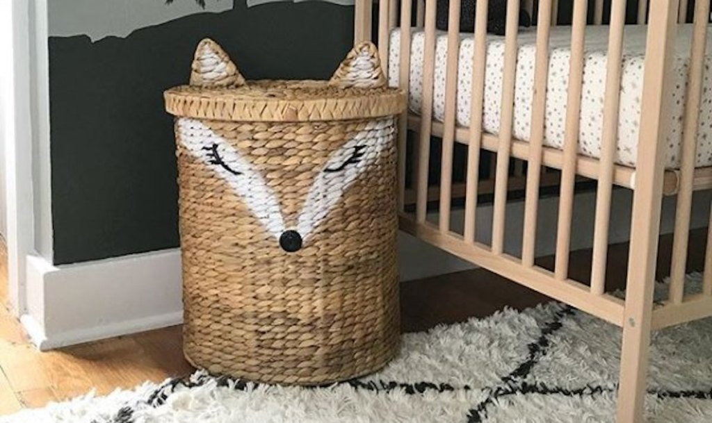 large fox shaped wicker basket sitting on rug next to crib