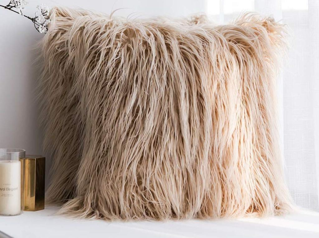 two tan beige brown faux fur throw pillows on bench