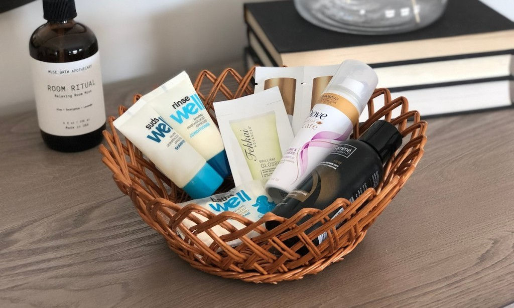 small basket with travel sized lotions shampoo conditioner soaps on top of dresser
