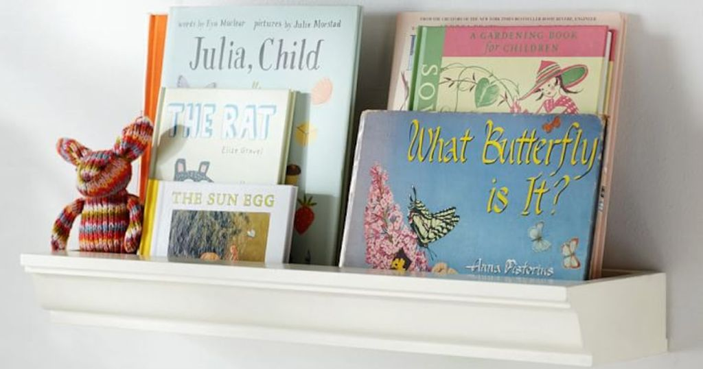 various different books on white floating shelf with plush toy