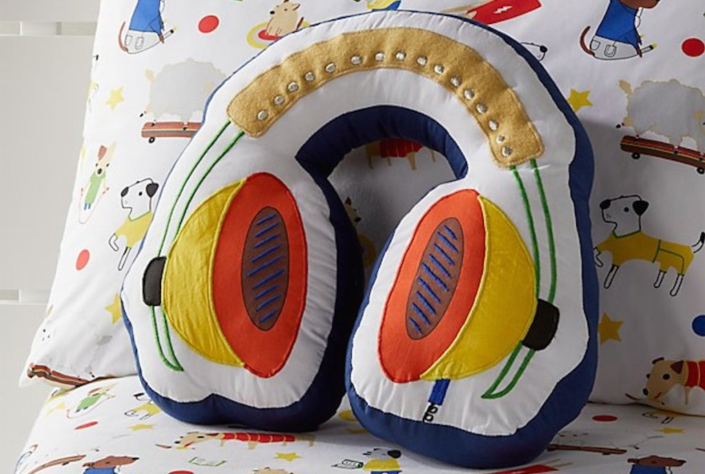 headphone shaped throw pillow on bed