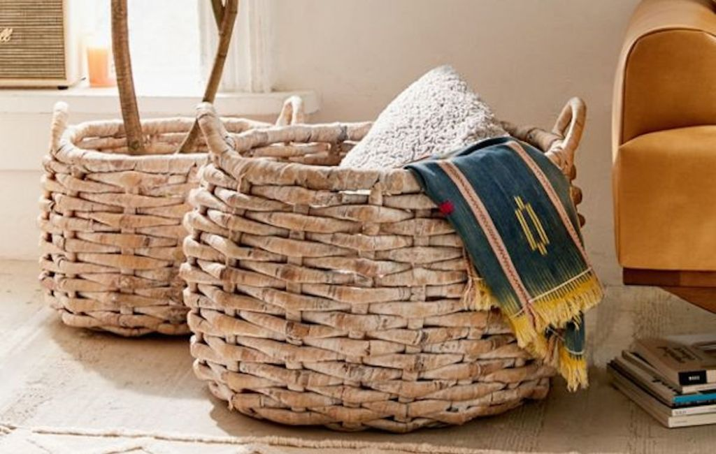large knotted natural color baskets sitting on floor with plant and blankets