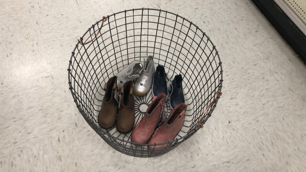 black wire basket sitting on floor with shoes inside