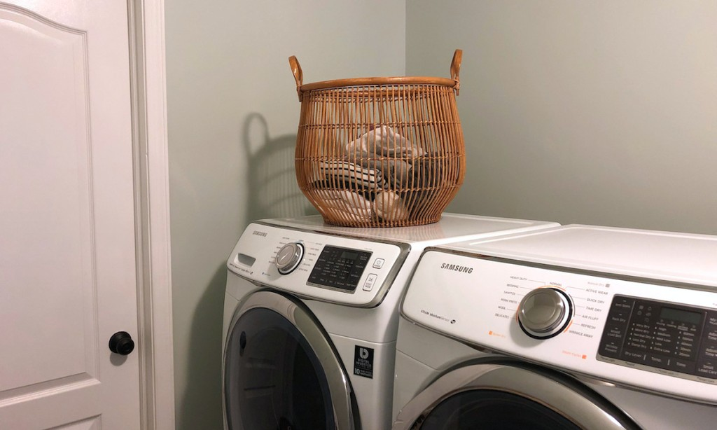 wicker laundry basket on top of washer and dryer