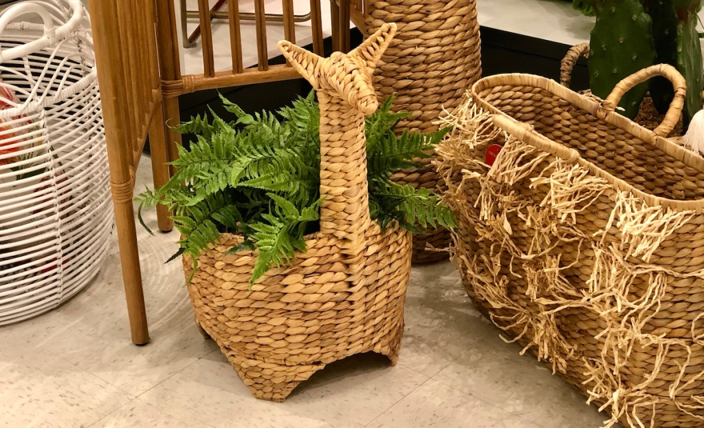 llama basket with a green faux plant inside sitting on the floor