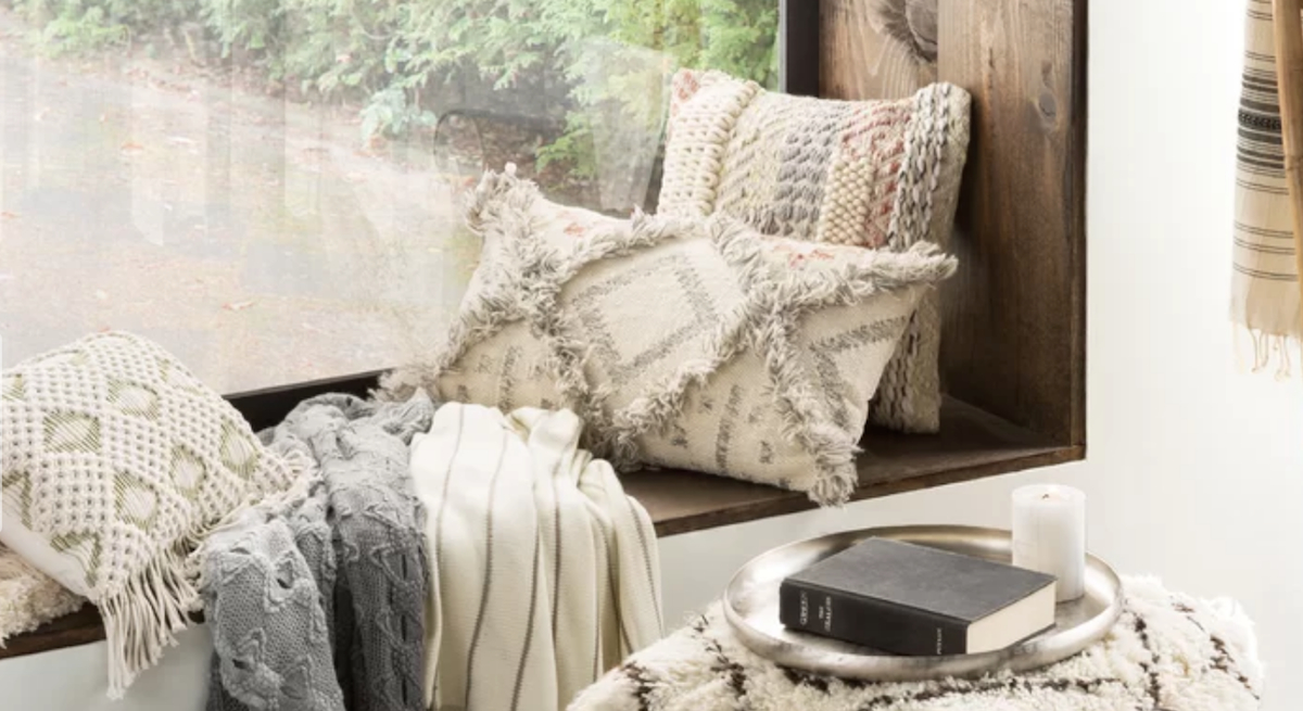 lumbar wool fringe pillow on window sill with other pillows throw blankets books on an ottoman