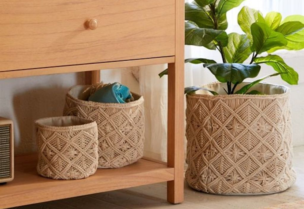 three macrame knotted baskets sitting on floor and console table with plant