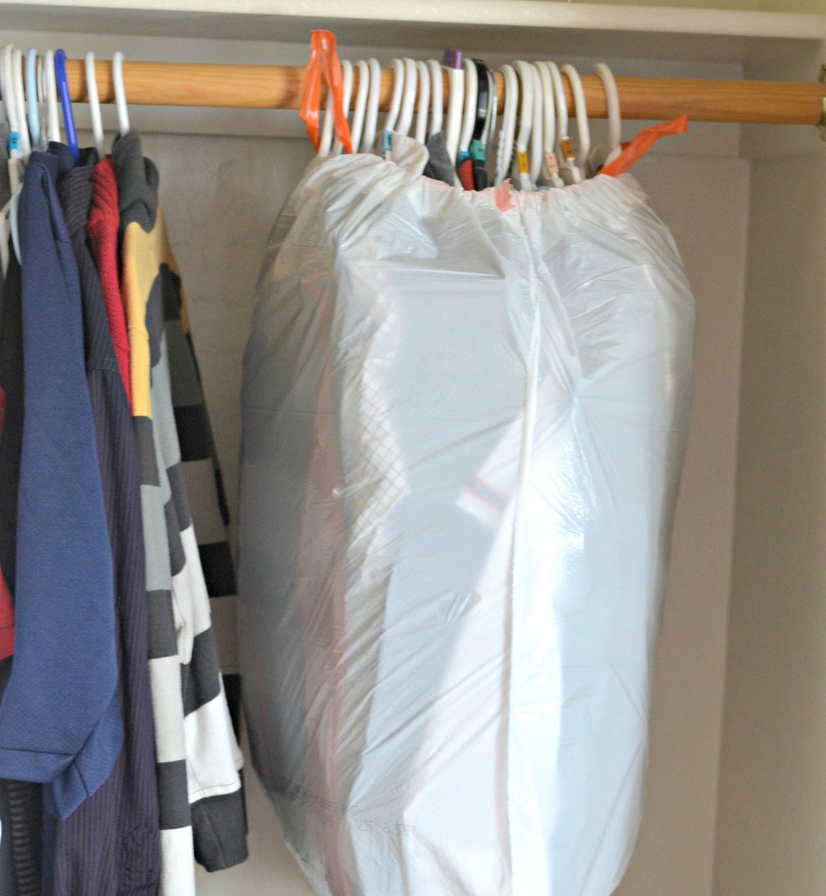 grouped clothes on hangers then wrapped in garbage bags