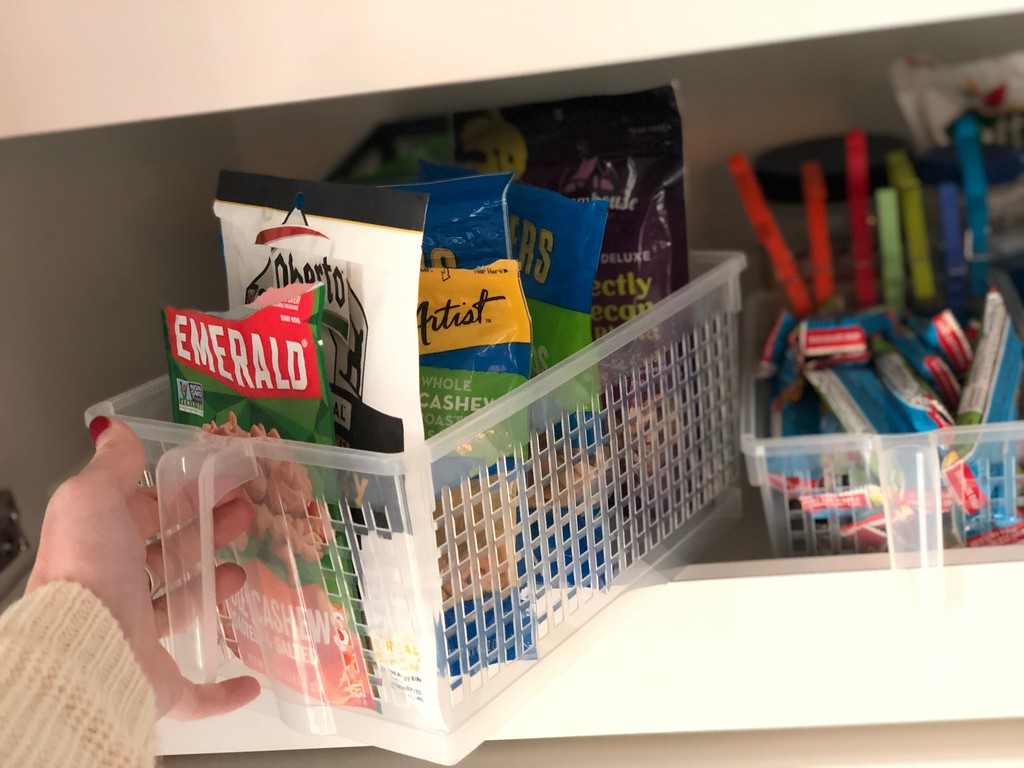 Pantry snacks stored in clear handled storage basket