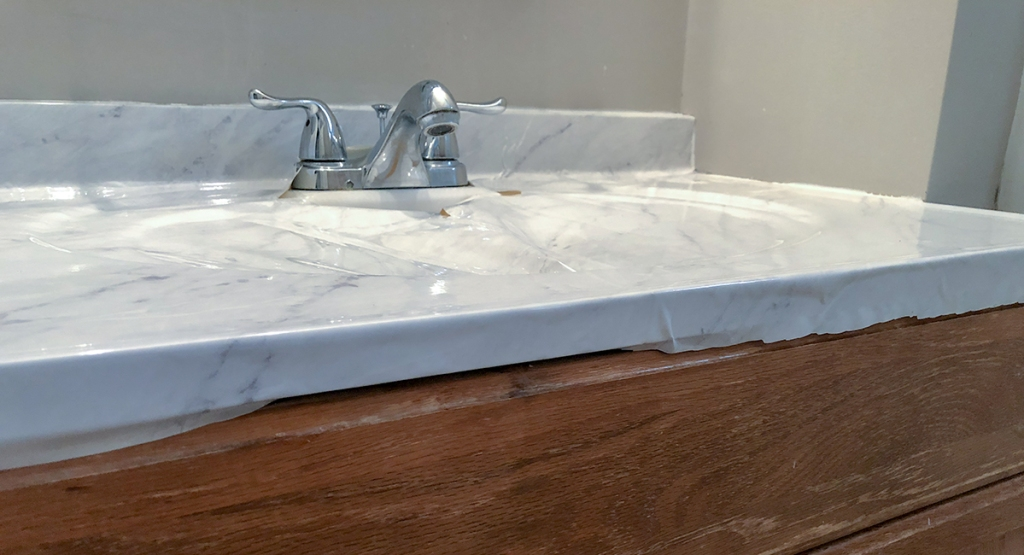 folding down edges of marble contact paper on countertop