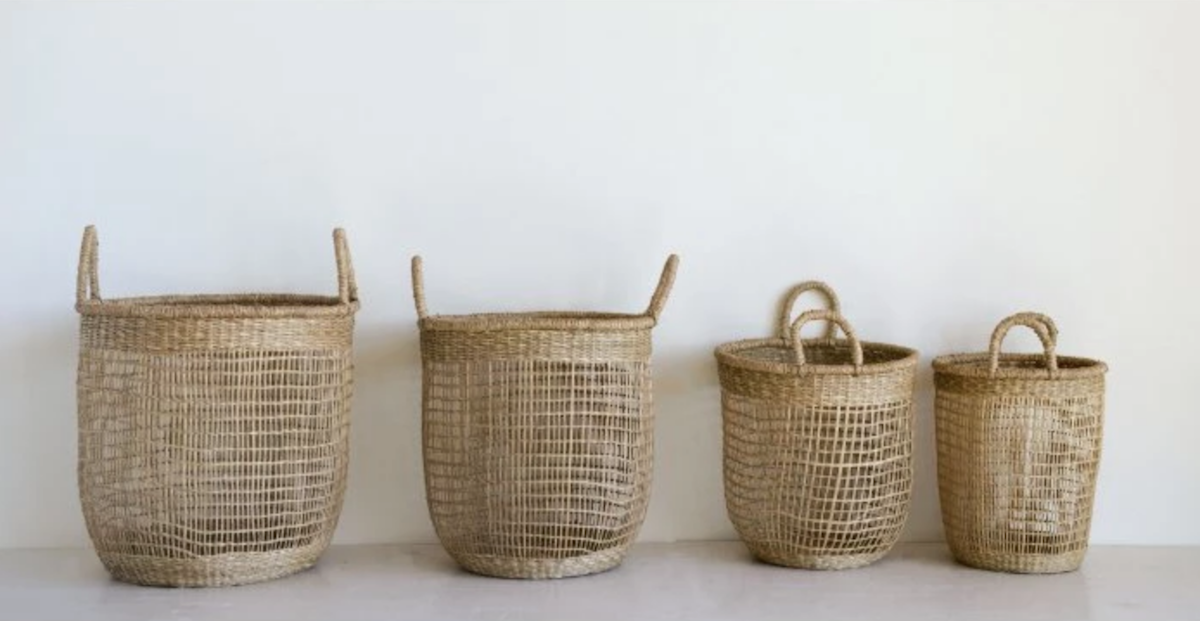 four seagrass baskets sitting in a row on the floor