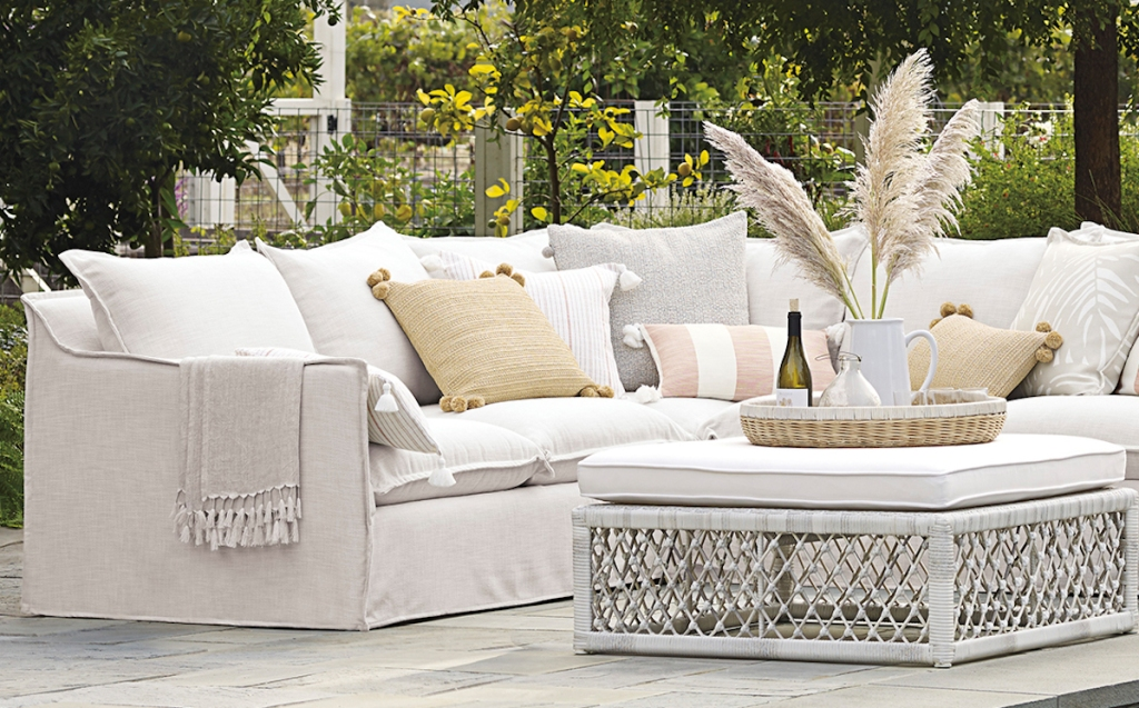 outdoors photo of off white couch by pool with pillows yellow and striped