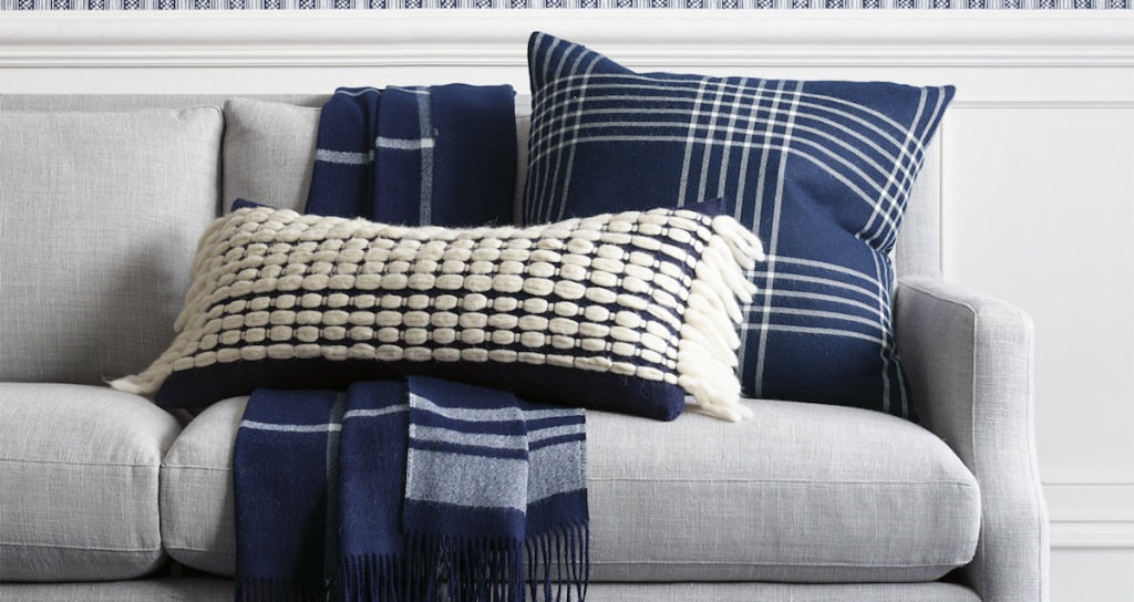 wool woven navy and cream off white lumbar pillow with tassel fringe on gray couch