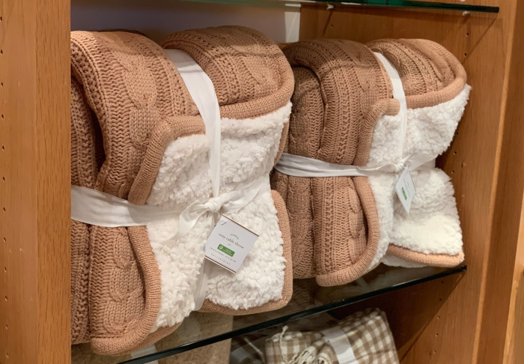 pottery barn tan camel cable knit throw blankets on shelf
