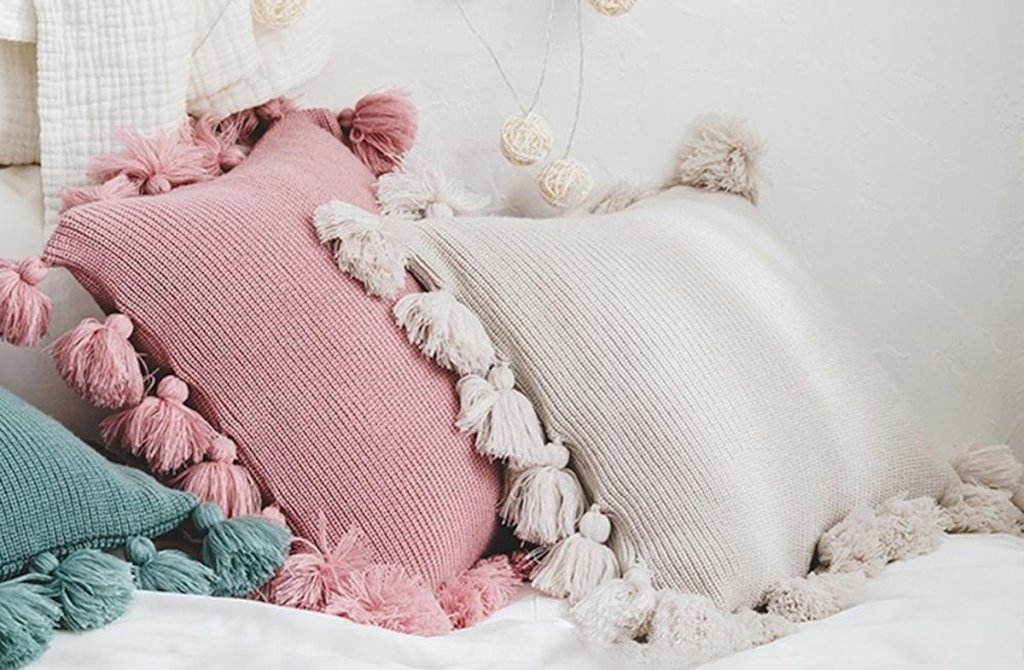 blue pink ivory white tassel pillows on a bed
