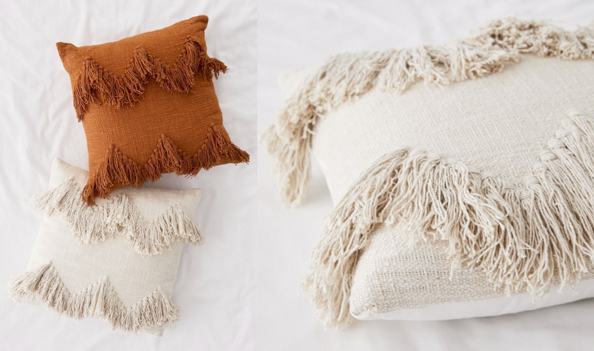 fringe tassel pillows on bed in terracotta cream, off white, ivory