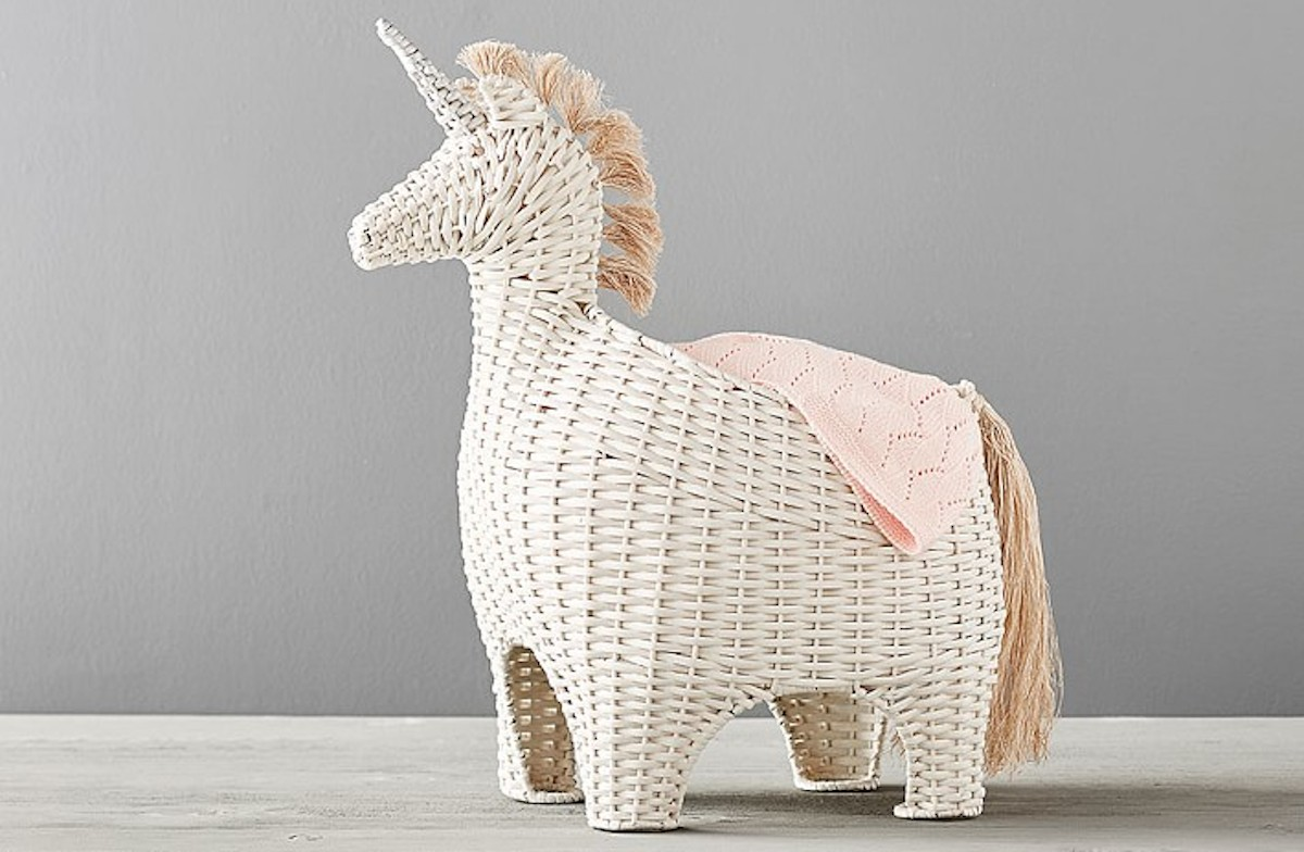 cream ivory unicorn wicker basket sitting on gray floor with blanket draped on the side