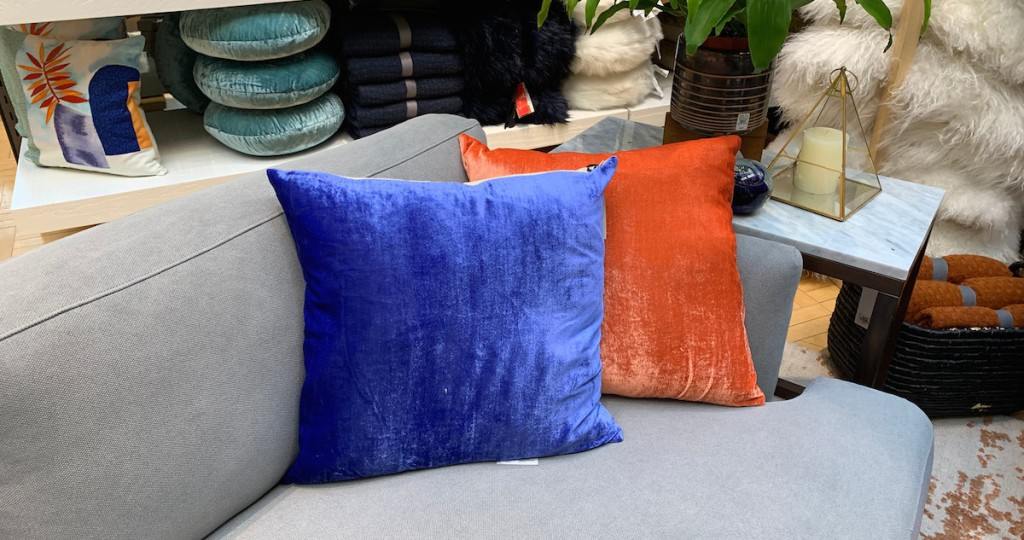 royal blue and bright orange velvet pillows sitting on a gray couch