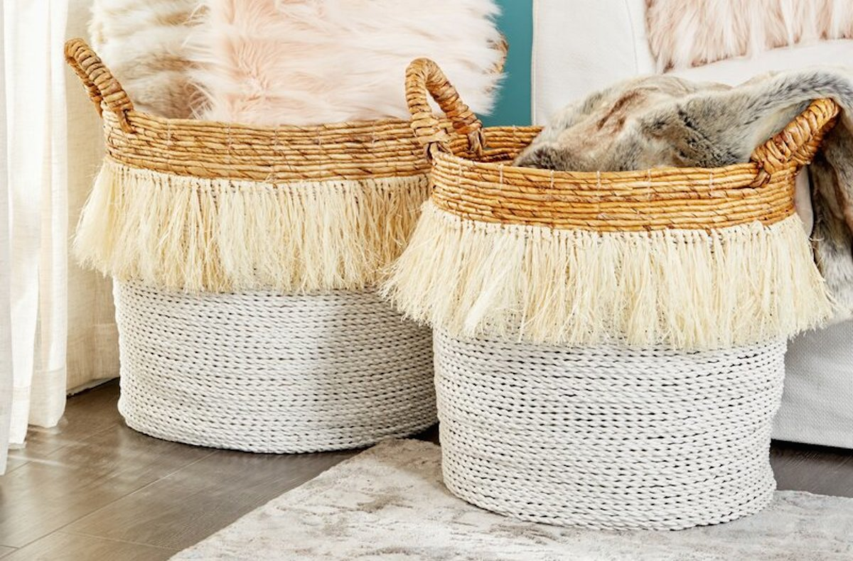 white yellow fringe two tone baskets on floor with pillows and blankets inside