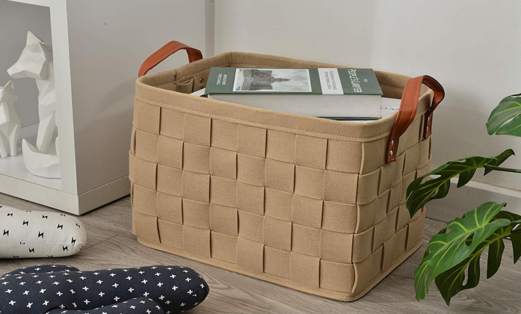 woven felt basket with leather handles sitting on floor with books