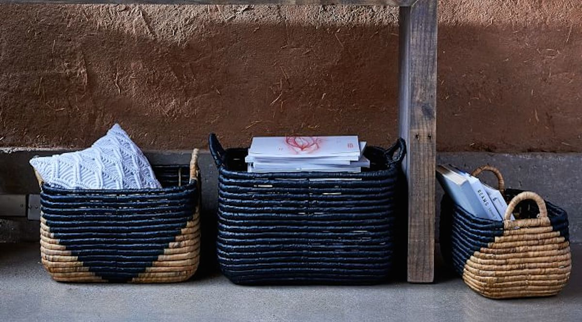 black and natural colored woven baskets sitting with magazines