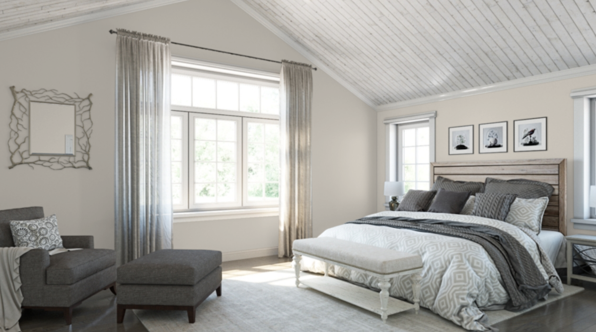 neutral colored bedroom with large bed, bench, accent chair and large open window