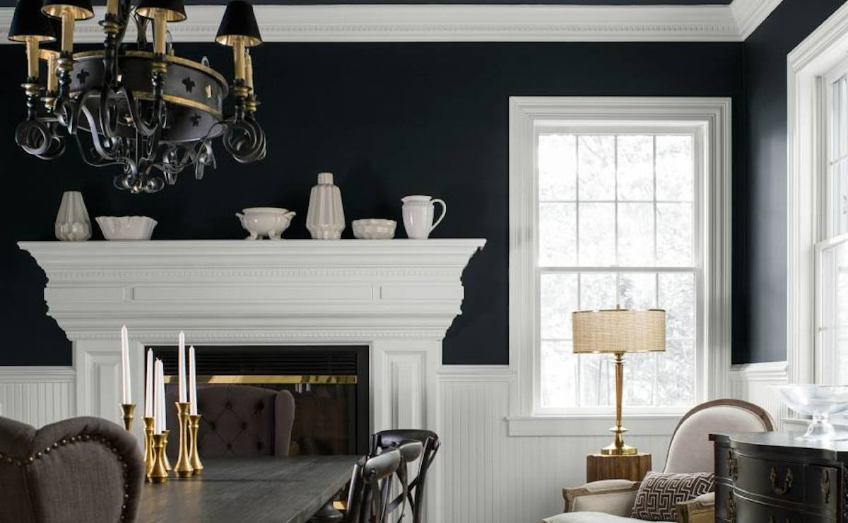 dining room with black walls and white trim with fireplace mantel and gold decor items