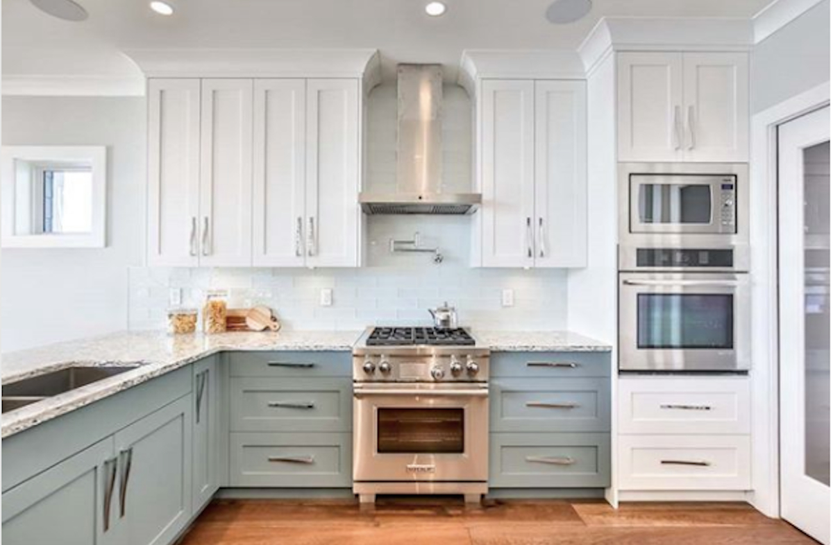 white and sage blue kitchen cabinets with stainless steel appliances