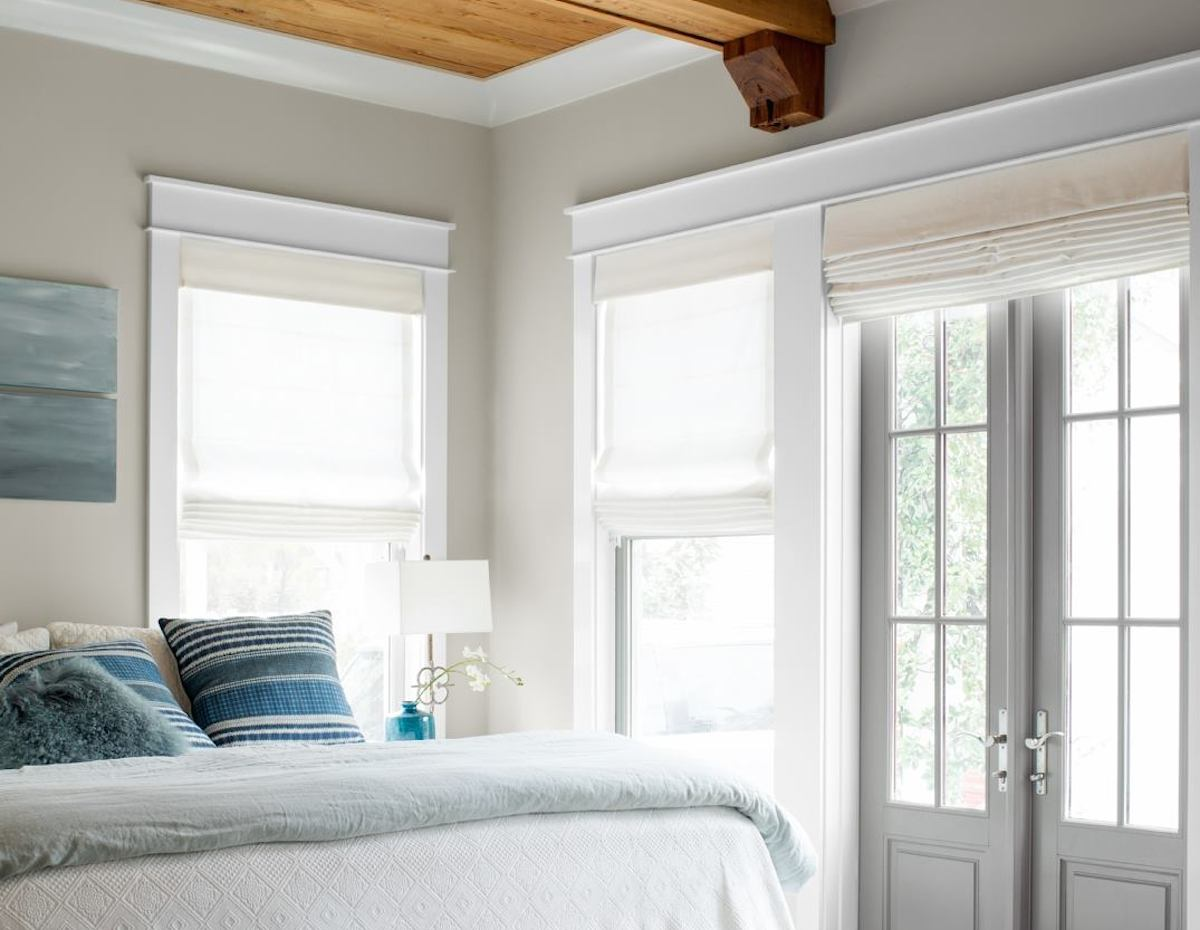 neutral color walls with windows wood ceiling and bed with blue stripe pillows gray french doors