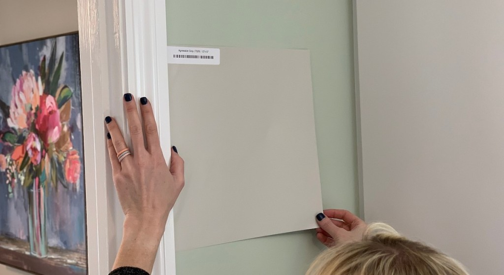 hands placing gray paint sample on wall floral artwork in background