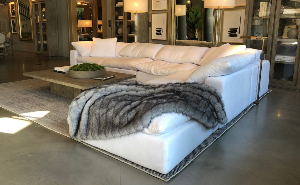 a white sectional couch with gray fur blanket on top with rug and coffee table