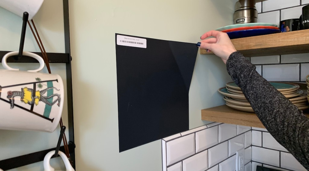 hand holding a black square wall sticker in kitchen with tile backsplash and mugs