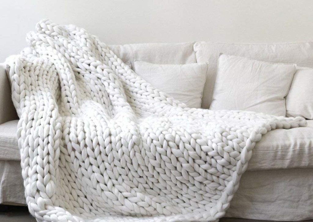 large white chunky knit blanket draped on an off white couch