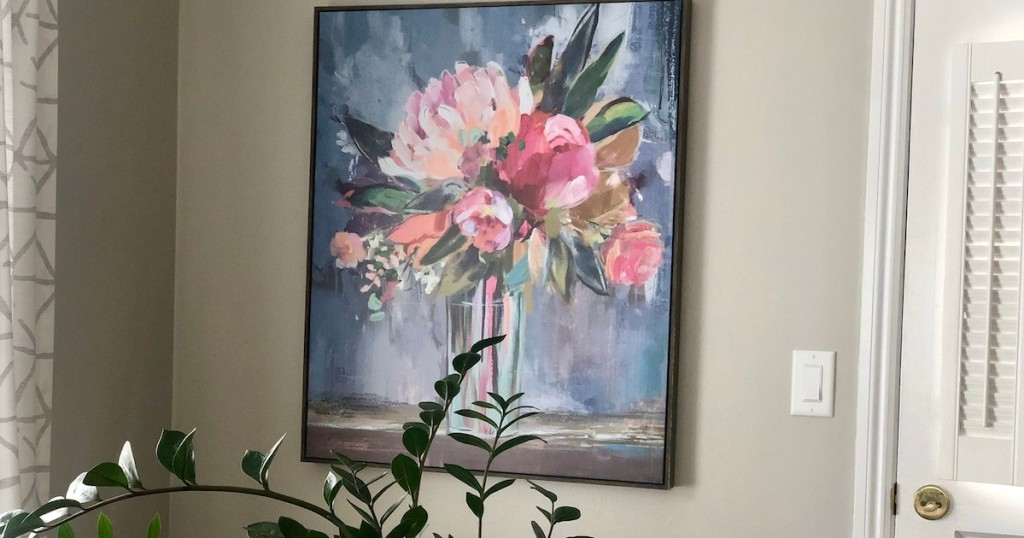 picture of floral artwork on beige wall with green stems in front