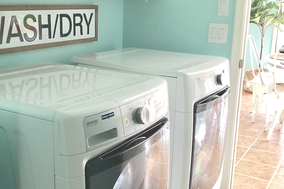 a bright blue laundry room with a front loader washer and dryer