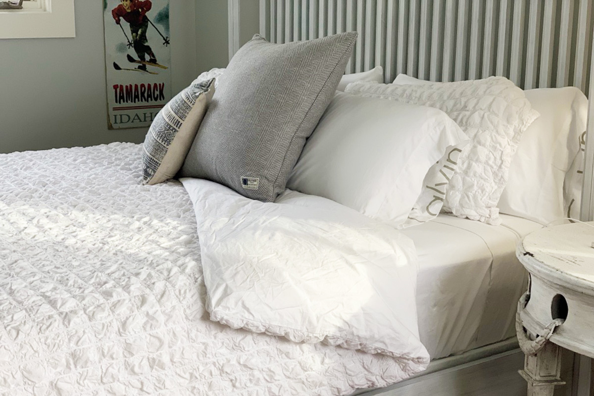 a bed made up with white sheets and a white duvet
