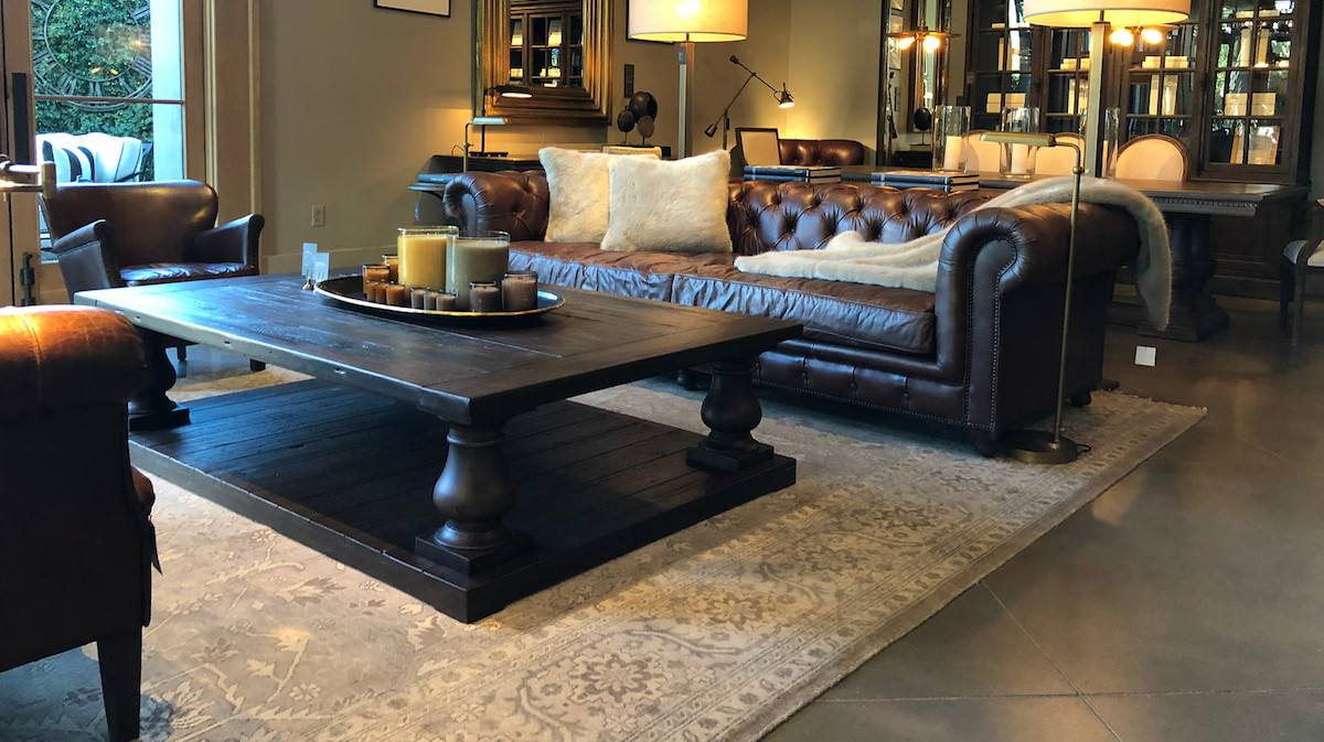 living room with large rug dark leather furniture couches and wood coffee table