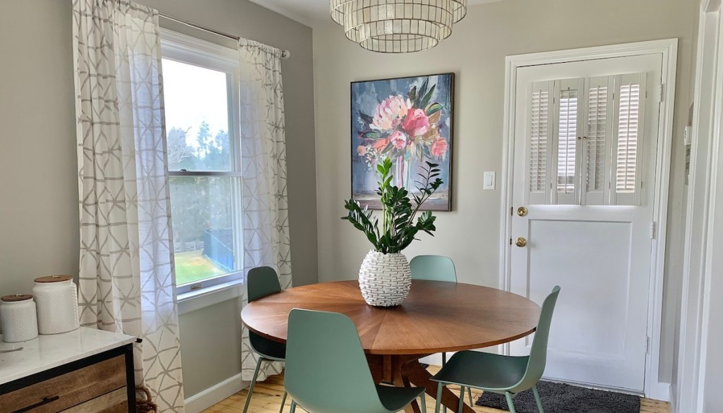 breakfast nook with flower artwork white curtains round wood table with blue green chairs